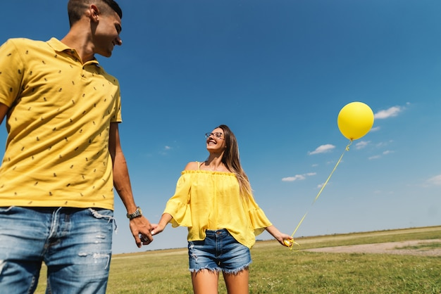 Bonito casal caucasiano de mãos dadas, eu campo e céu. mulher segurando balão amarelo. dominando as cores azuis e amarelas.