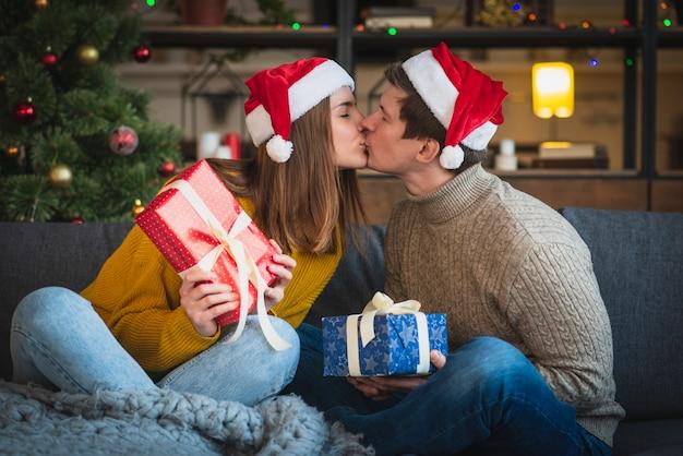 Bonito casal de natal segurando presentes beijando