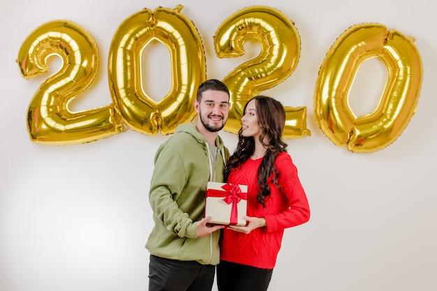 Bonito casal homem e mulher com presente de natal na frente de 2020 balões de ano novo