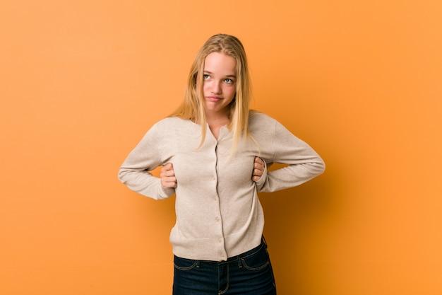Bonito caucasiano adolescente posando em pé contra um fundo laranja