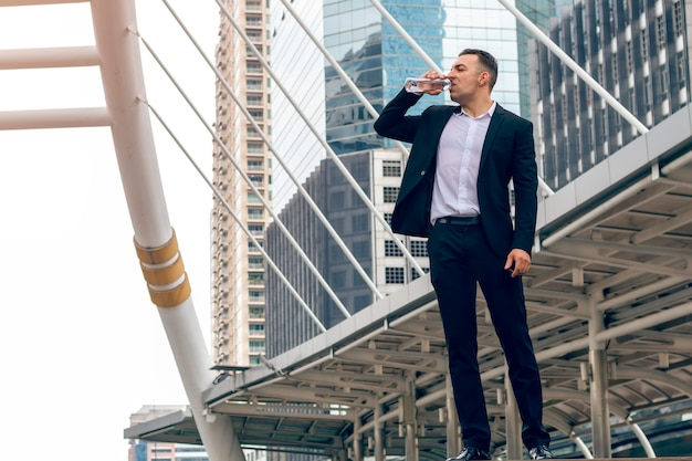 Bonito caucasiano empresário relaxar e beber água na cidade.