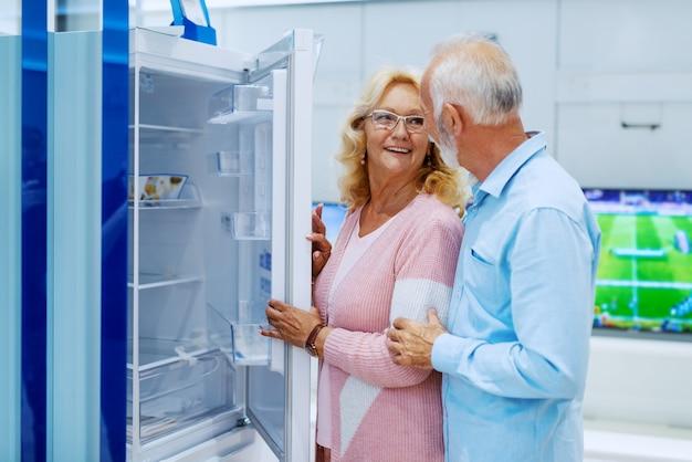 Bonito caucasiano sorridente feliz sênior escolhendo novo frigorífico para sua casa. interior da loja de tecnologia.