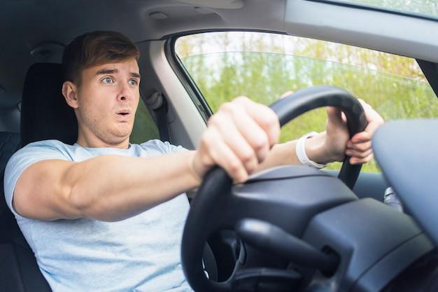 Bonito com medo cara, motorista, jovem assustado chocado prestes a ter um acidente de trânsito, dirigindo o carro na estrada, segurando o volante do automóvel. desapertado pelo cinto de segurança. violação de tráfego