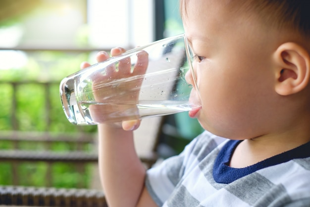 Bonito com sede asiática 2 anos de idade criança bebê menino criança segurando e bebendo um copo de água