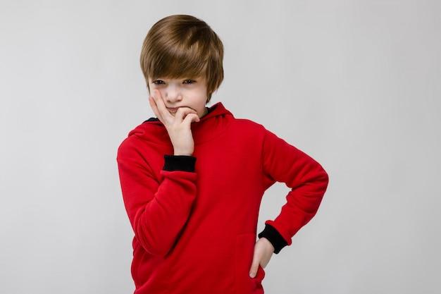 Bonito confiante caucasiano suspeito menino de suéter vermelho sobre fundo cinza