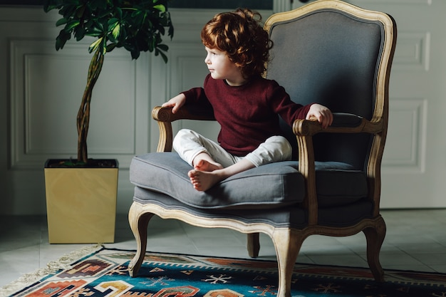 Bonito, curly, menino sentando, relaxado, em, confortável, poltrona, e, olhando
