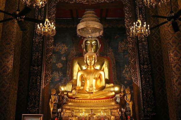 Bonito da estátua dourada da buda e da arquitetura tailandesa da arte no templo de tailândia.