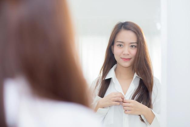 Bonito da mulher asiática do retrato que olha no espelho no quarto.