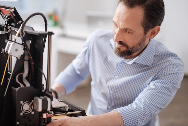 Bonito designer profissional masculino olhando para a impressora 3d e criando um novo design enquanto trabalha com a tecnologia 3d