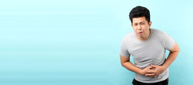 Bonito do homem asiático doente tem dor de estômago isolada na parede azul.