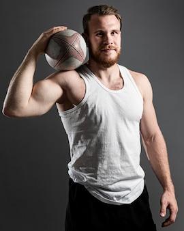 Bonito e atlético jogador de rúgbi segurando uma bola enquanto posa
