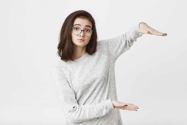 Bonito e atraente modelo jovem mostrando algo com as mãos, usando óculos e levantando as sobrancelhas