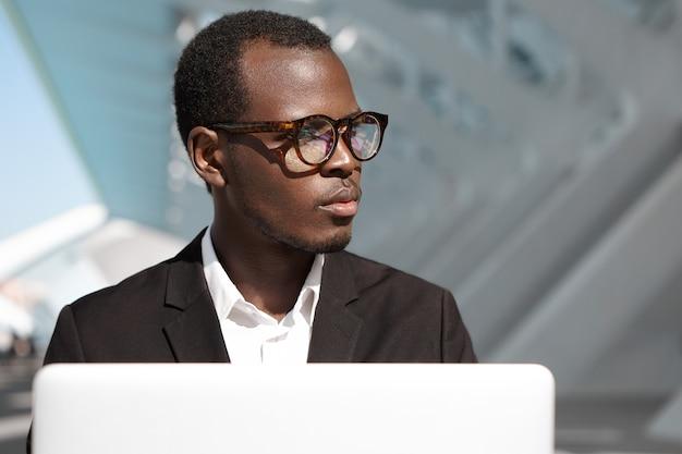 Bonito e bem sucedido jovem trabalhador corporativo afro-americano de óculos e terno preto, sentado ao ar livre na frente do laptop, olhando para longe, tendo expressão pensativa, absorvido em questões de negócios
