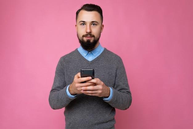 Bonito e bonito moreno barbudo jovem vestindo um suéter cinza e uma camisa azul isolada em rosa