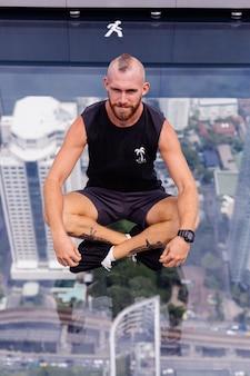 Bonito e brutal homem barbudo caucasiano no chão de vidro em bangkok