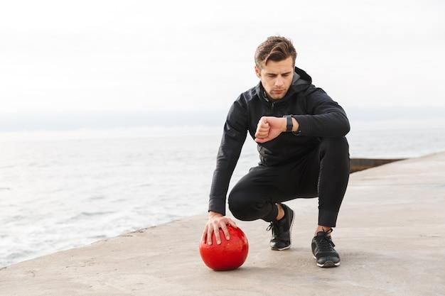 Bonito e confiante jovem esportista malhando na praia, fazendo exercícios com uma bola pesada, olhando para o smartwatch