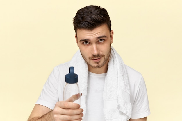 Bonito e confiante jovem europeu com cerdas posando com uma toalha branca em volta do pescoço, bebendo água de um copo de plástico após o treinamento físico