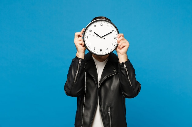 Bonito e elegante jovem com a barba por fazer na jaqueta de couro preta e camiseta branca segurando o relógio redondo isolado no retrato de estúdio de fundo de parede azul. conceito de estilo de vida de pessoas. se apresse. simule o espaço da cópia.