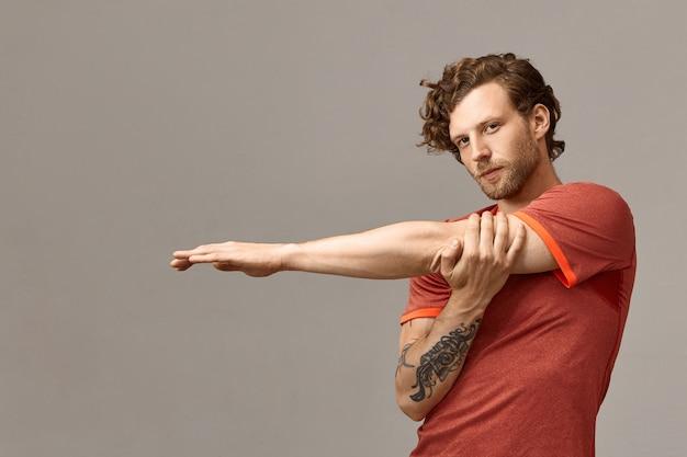Bonito e elegante jovem esportista europeu com barba por fazer, com tatuagem e cabelo ruivo cacheado que estica os músculos dos braços, aquecendo o corpo antes de fazer exercícios aeróbicos com confiança