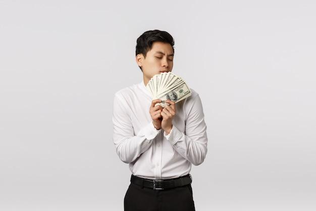 Bonito e feliz asiático cara beijando dinheiro, cheirando dólares ou dinheiro satisfeito, ganhar o prêmio, fez um bom negócio, alcançar a estabilidade financeira, pronto comprar carro novo