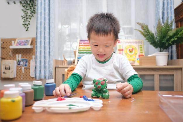 Bonito e feliz pequeno asiático de 3 a 4 anos de idade, criança, menino, criança pintando a cor em um brinquedo de gesso diy, estátua de gesso 3d interna em casa, conceito de jogo criativo para crianças e bebês - foco seletivo