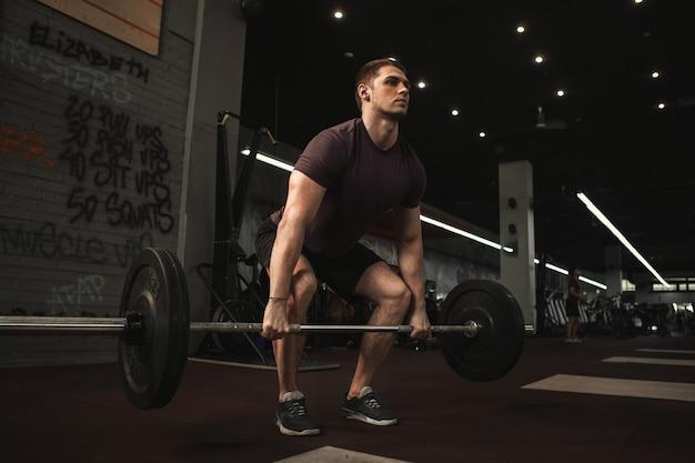 Bonito e jovem atleta do sexo masculino fazendo exercícios de levantamento terra no ginásio de treinamento funcional