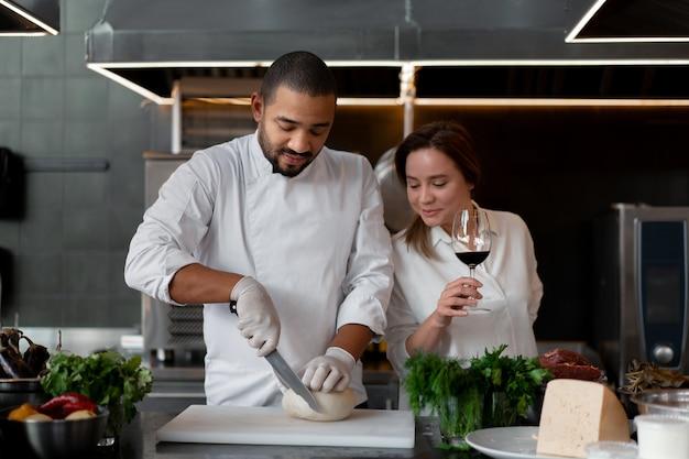 Bonito e jovem chef africano cozinhando com a namorada na cozinha