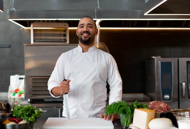 Bonito e jovem chef africano em pé na cozinha profissional em restaurante preparando uma refeição de carne e queijo vegetais. retrato de homem em uniforme de cozinheiro. conceito de alimentação saudável.