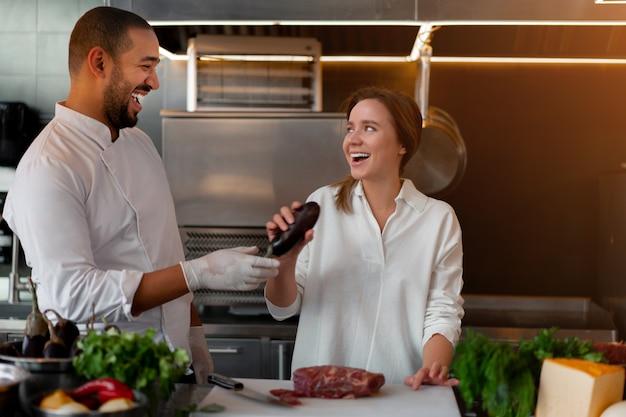 Bonito e jovem chef africano está cozinhando com uma namorada caucasiana na cozinha um cozinheiro ensina uma garota a cozinhar. homem e mulher cozinhando na cozinha profissional. relacionamento interracial