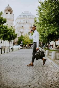 Bonito e jovem empresário afro-americano usando um telefone celular enquanto corta a rua
