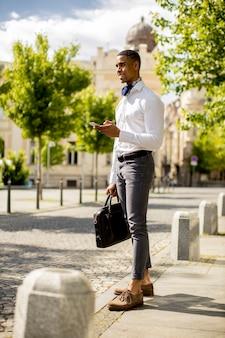 Bonito e jovem empresário afro-americano usando um telefone celular enquanto espera por um táxi em uma rua