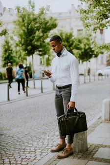 Bonito e jovem empresário afro-americano usando um telefone celular enquanto espera por um táxi esperando um táxi em uma rua