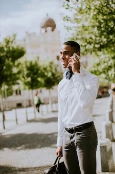 Bonito e jovem empresário afro-americano usando um telefone celular enquanto espera por um táxi na rua