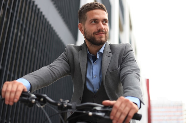 Bonito e jovem empresário andando de bicicleta ao ar livre na cidade.