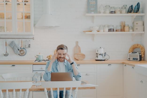 Bonito e jovem empresário com roupas casuais, trabalhando remotamente com o computador, enquanto está sentado à mesa de madeira na elegante cozinha interior e sorrindo, olhando para a tela do laptop com expressão satisfeita