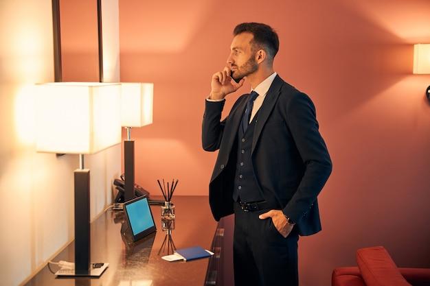 Bonito e jovem empresário de terno em frente a um espelho olhando seu reflexo enquanto fala ao telefone