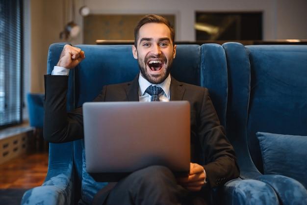 Bonito e jovem empresário de terno sentado no saguão do hotel, usando um laptop, comemorando