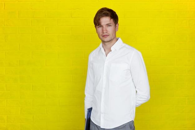 Bonito e jovem empresário em camisa segurando um laptop, olhando para a câmera, sobre fundo amarelo.