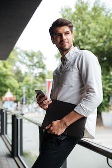 Bonito e jovem empresário em pé e usando o celular ao ar livre