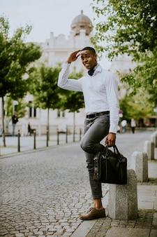 Bonito e jovem empresário esperando um táxi em uma rua