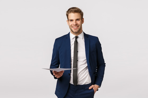 Bonito e jovem empresário rico em terno clássico, segurando papéis e sorrindo, tendo reunião de negócios discutir equipe de finanças com parceiros, gerenciar empresas, permanente fundo branco