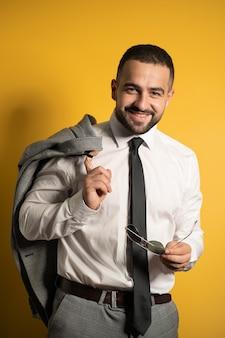 Bonito e jovem empresário segurando os óculos de sol na mão e a jaqueta no ombro em pé isolado no fundo amarelo.