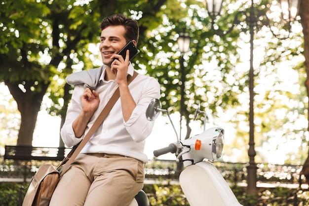 Bonito e jovem empresário sentado em uma moto ao ar livre, falando no celular