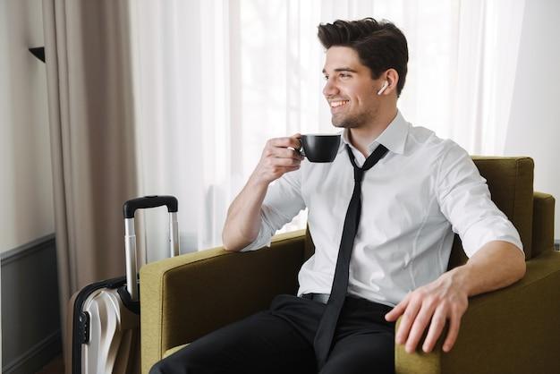 Bonito e jovem empresário sentado na poltrona de um hotel com uma mala, tomando uma xícara de café