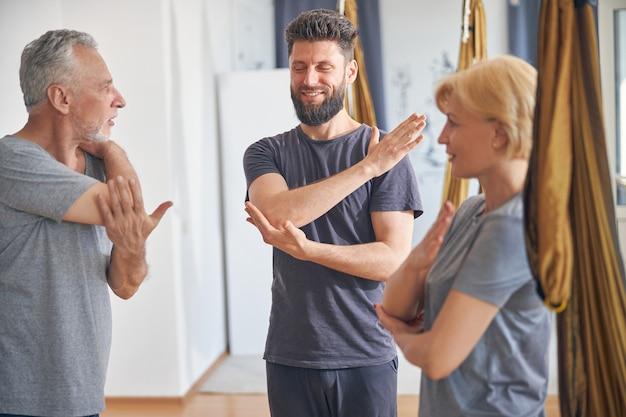 Bonito e jovem treinador branco qualificado, instruindo seus clientes durante os alongamentos de ombro em uma academia