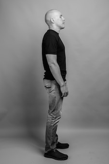 Bonito e musculoso careca vestindo camisa preta contra parede cinza em preto e branco