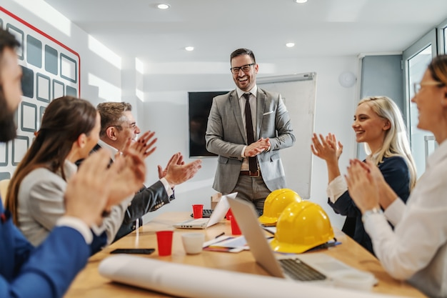 Bonito e orgulhoso empresário caucasiano teve uma excelente apresentação na sala de reuniões. seus colegas batendo palmas e sorrindo.