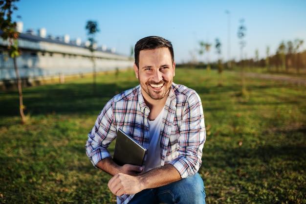 Bonito e sorridente agricultor caucasiano em jeans e camisa xadrez, agachado ao ar livre com o tablet nas mãos.
