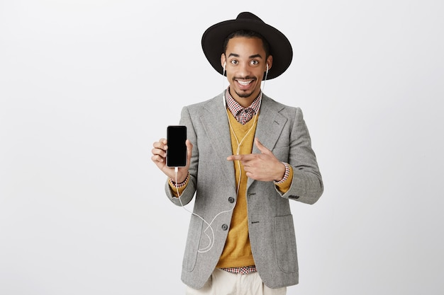 Bonito e sorridente negro de terno e chapéu moderno, ouvindo música em fones de ouvido, apontando o dedo para a tela do smartphone