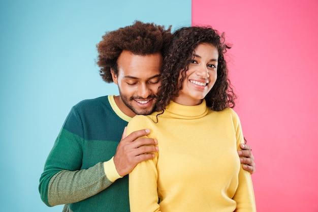 Bonito e terno casal africano em pé e se abraçando sobre um fundo rosa e azul